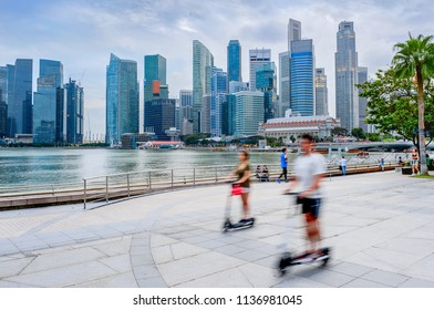 Modern skyline of Singapore with skyscrapers, people riding scooters at city embankment