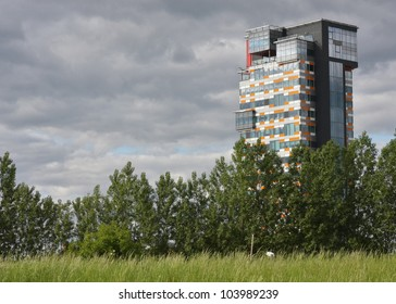 Modern skyscraper appearing behind meadows and trees. Symbol for urbanisation.