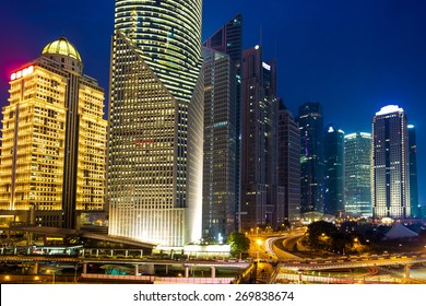 modern skyscrapers and urban street at night