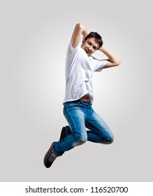 Modern slim hip-hop style man jumping dancing on a grey background