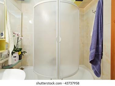 Modern small shower-bath with blue towel