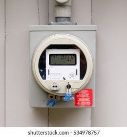Modern smart grid residential digital power supply meter mounted outside on house wall