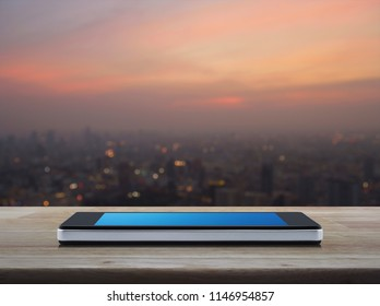Modern smart mobile phone with blank blue screen on wooden table over blur of cityscape on warm light sundown, Business communication concept