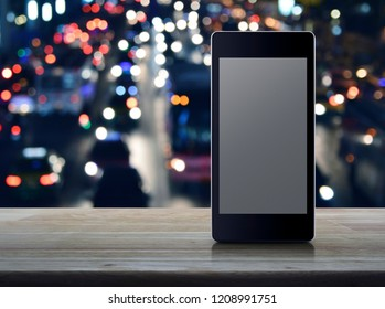 Modern smart mobile phone with blank grey screen on wooden table over blur colorful night light city with cars in city