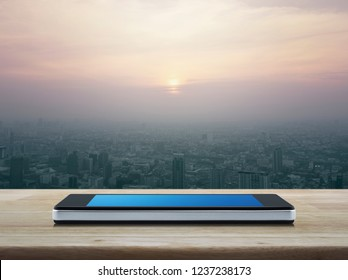 Modern smart mobile phone with blank blue screen on wooden table over city tower and skyscraper at sunset, vintage style, Business communication concept