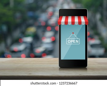 Modern smart mobile phone with online shopping store graphic and open sign on wooden table over blur of rush hour with cars and road, Business shop online concept