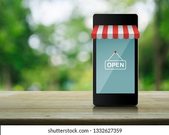 Modern smart mobile phone with online shopping store graphic and open sign on wooden table over blur green tree in park, Business shop online concept