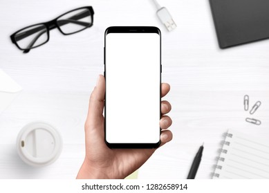 Modern smart phone ih hand with isolated, blank display for mockup, ap design presentation. Office desk in background.