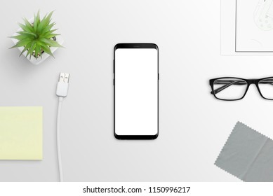 Modern smart phone with round edges on white desk. Isolated screen for mockup.