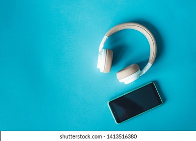 Modern smartphone in blue case with awesome wireless headphones on lazure textured background with copy space