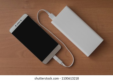 A modern smartphone and a connected power bank on a wooden background.