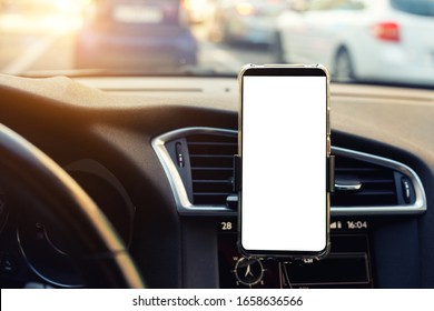 Modern smartphone device gadget mounted on phone holder at car dashboard. Mock-up white screen isolated template. Copyspace for text . Vehicle interior cockpit view. Traffi jam info app