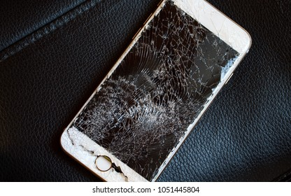 Modern smartphone with highly broken screen on black background.