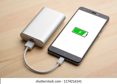 Modern smartphone lays on light wooden table while charging with power bank with quick charge. Illustration of green battery with lightning is on the mobile phone screen while charging