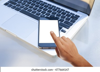Modern smartphone on a laptop keyboard. Finger pointing at screen. Blank display replaceable with needed design.Vertical mockup