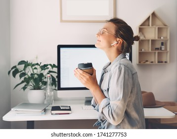 Modern smiling beautiful woman working and drinking coffee from reusable mug at home office. Minimalist slow life style workplace of creative female in glasses and earphones using computer technology.