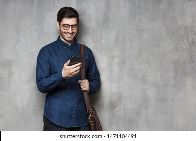 Modern smiling businessman standing against gray textured wall with copy space, holding phone in hand and bag on shoulder