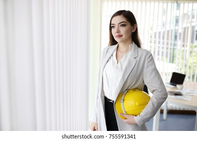 Modern  Smiling Pretty Business Woman With Arms Crossed in the office with copy space, Digital composite of Happy businesswoman standing against city background. good news well done negotiating.
