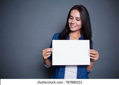 Modern smiling woman in a jeans shirt with blank sheet of paper for advertising in hands on a gray background isolated.