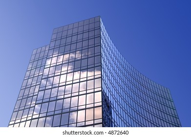 Modern smoked glass office building set against a blue sky.