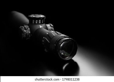 Modern sniper scope on a dark background. Optical device for aiming and shooting at long distances.