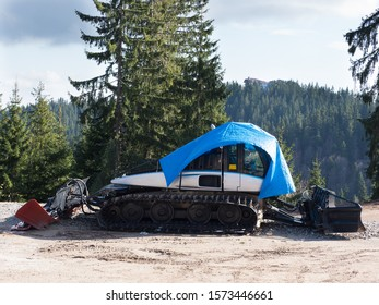 A modern snow plough with caterpillar tracks is partially covered in a blue tarpaulin ready to start clearing snow.Pine trees and sky in background.Image