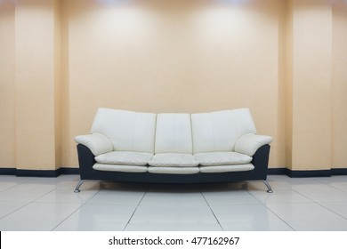 modern sofa  black and white color stand on the living room and orange wall background with ceiling lights on top.