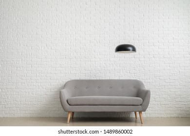 Modern sofa near white brick wall