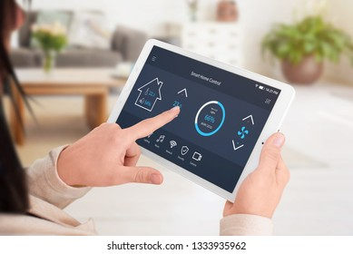 Modern software to home control on tablet display. Woman control temperature in living room. Close-up.