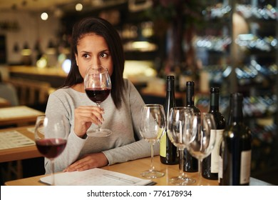Modern sommelier holding glass of red wine and evaluating its smell while comparing it with other sorts