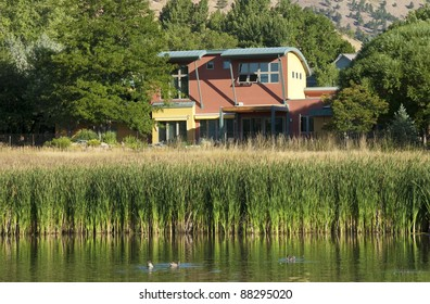 Modern southwest architecture home at the shore of a little lake with ducks