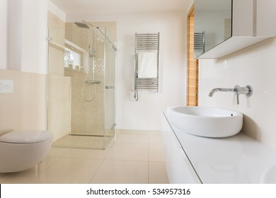 Modern spacious bathroom with bright tiles with glass shower, toilet and sink