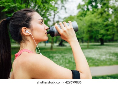 Modern sporty woman drinking water after running