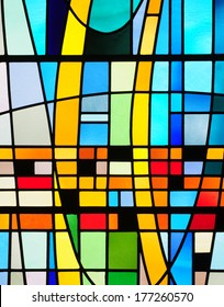 Modern stained glass window with abstract design in colors of blue, yellow, green and orange