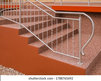 Modern stainless steel railing on outside staircase with stone carpet in red-brown