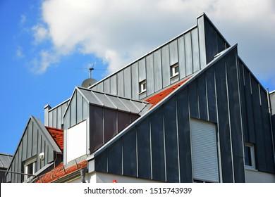 Modern Standing Seam Metal Facade and tiled Roof with Dormer Windows, Snow Guard an Rain Gutter