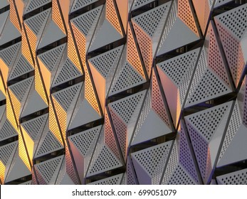 modern steel cladding with angular geometric patterns  and square holes in a shiny metallic finish with colored reflection