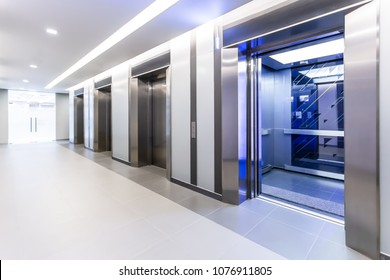 Modern steel elevator doors opened cabins in a business lobby or Hotel, Store, interior, office,perspective wide angle. Four elevators in hotel lobby.