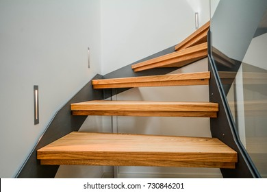 Modern steel staircase with wooden steps in a new apartment in a residential building