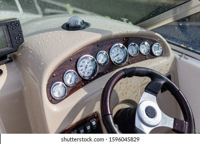 Modern steering wheel on dashboard background of luxury pleasure yacht, gps navigation, clock, compass, sounder, sonar, driving speed. Steering wheel in drops of rain and water motor boat
