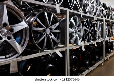modern store with alloy wheels and tires, indoors in shop. a lot of discs for automobile, big assortment