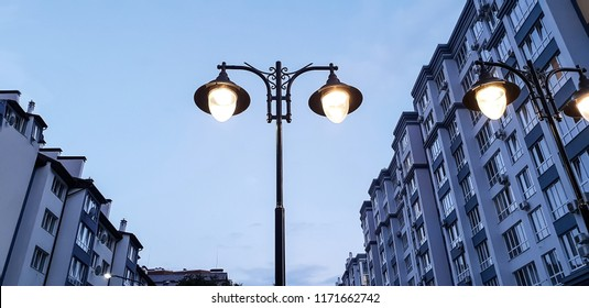 modern street lamp shines against a background of blue sky at sunset