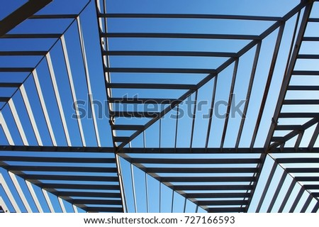 Modern strut construction between buildings, view from the ground to the blue sky