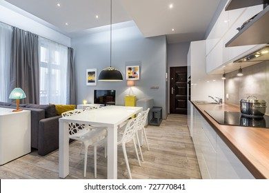 Modern studio flat with kitchenette, dining table, sofa and tv