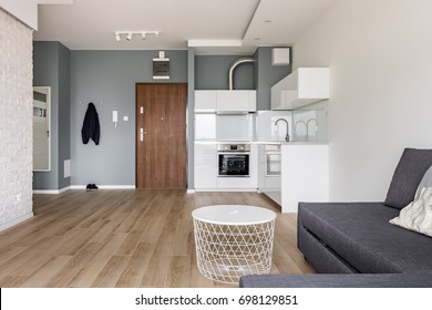 Modern studio flat with small kitchen, sofa and round coffee table