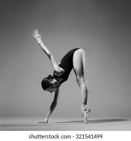 Modern style ballet dancer posing on studio background. Extreme flexibility, grayscale image.