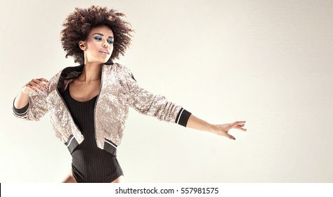 Modern style dancer with afro on her head jumping in studio.