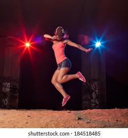 Modern style dancer jumping outdoors