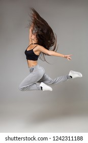 Modern style dancer posing on studio background. Hip hop, jazz funk, dancehall
