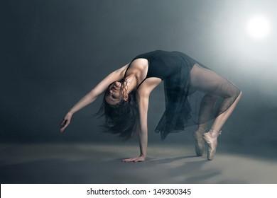 Modern style dancer posing on a studio grey background in fog